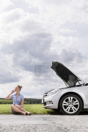 Photo for Mid adult businesswoman on call while sitting beside broken down car in countryside - Royalty Free Image