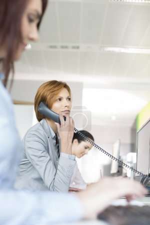 Photo pour Sourire jeune femme d'affaires en utilisant le téléphone fixe dans le bureau - image libre de droit