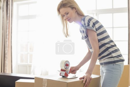 Photo for Woman packing moving box at home - Royalty Free Image