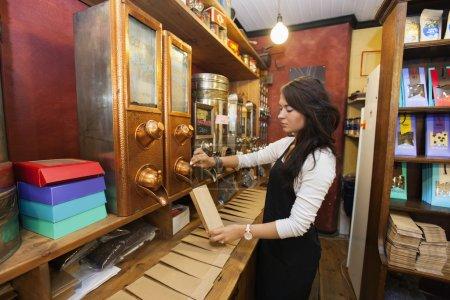 saleswoman dispensing coffee beans