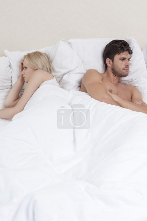 Couple avoiding each other in bed