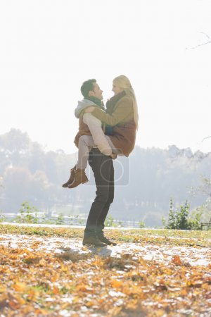 Photo for Young man lifting woman in park during autumn - Royalty Free Image