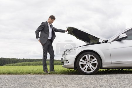 Photo for Young businessman examining broken down car engine in countryside - Royalty Free Image