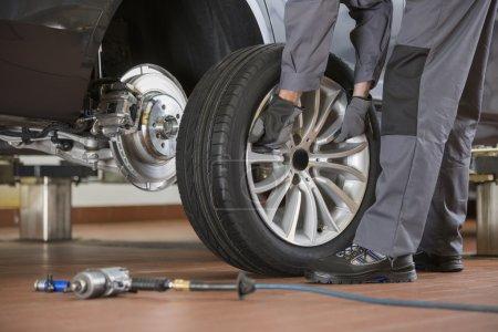 Photo pour Mécanicien masculin réparer le pneu de voiture dans l'atelier de réparation - image libre de droit