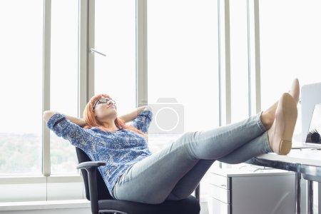Photo pour Femme d'affaires relaxant avec les pieds au bureau dans le bureau créatif - image libre de droit