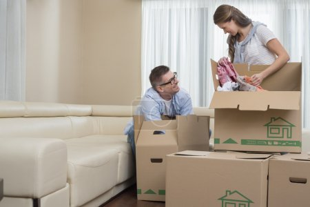 Photo for Happy couple unpacking cardboard boxes in new home - Royalty Free Image