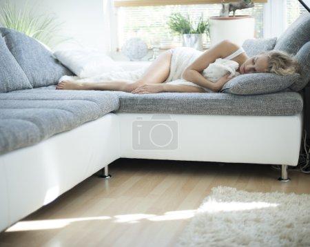 Photo pour Jeune femme blonde dormant sur le canapé à la maison - image libre de droit