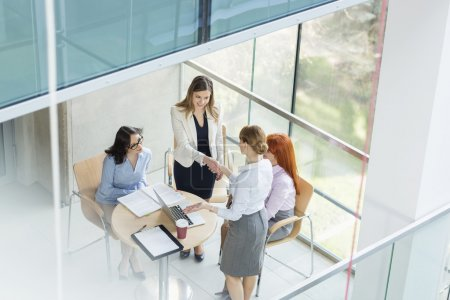 Photo for Businesswomen shaking hands at table in office - Royalty Free Image