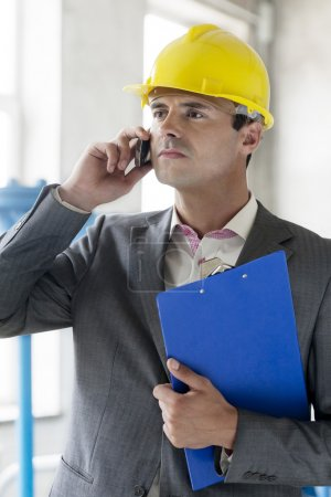 Supervisor with clipboard using cell phone