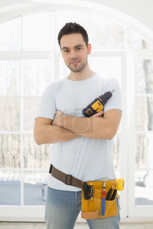 Man with hand drill standing in new house