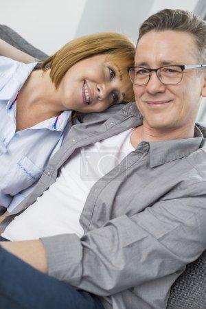 Loving couple sitting on sofa