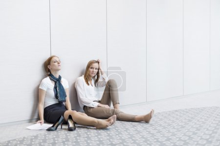 Photo for Frustrated businesswomen sitting on floor in office - Royalty Free Image
