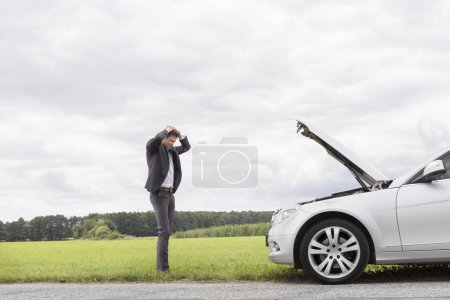 Photo for Sad young businessman standing with hands on head near broken car in countryside - Royalty Free Image