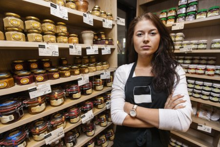 Photo for Portrait of confident saleswoman standing arms crossed in grocery store - Royalty Free Image