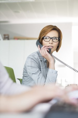 Photo for Young businesswoman using telephone in office - Royalty Free Image