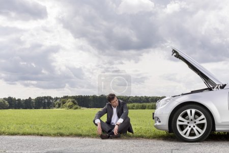 Photo for Unhappy young businessman sitting by broken down car in countryside - Royalty Free Image