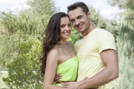 Photo pour Couple de jeune romantique embrassant dans parc - image libre de droit