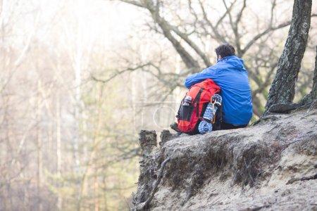 hikersitting on edge of cliff