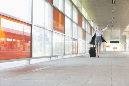 Businesswoman with luggage rushing