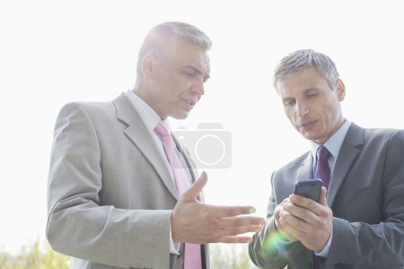 Businessmen discussing over mobile phone