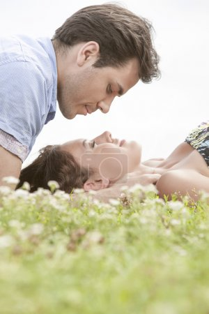 Photo for Young man looking at woman sleeping on grass against sky - Royalty Free Image