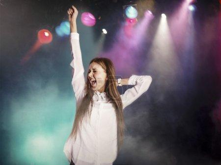 Photo pour Jeune femme excitée dansant dans une boîte de nuit - image libre de droit