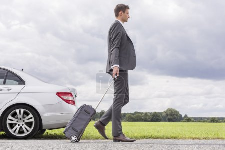 Photo for Young businessman with suitcase leaving broken down car in countryside - Royalty Free Image