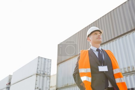 Worker standing against cargo containers