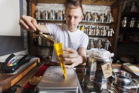 Photo pour Vendeur scooping ingrédient dans un sac en papier au magasin de thé - image libre de droit