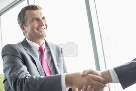 Photo for Smiling mature businessman shaking hands with partner in office - Royalty Free Image