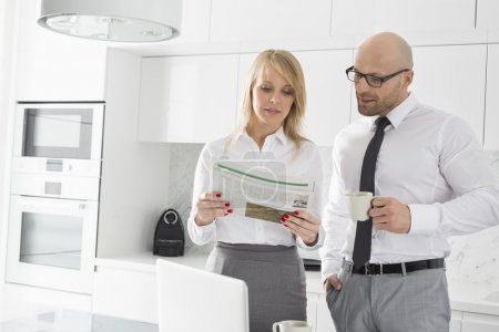 Business couple reading newspaper