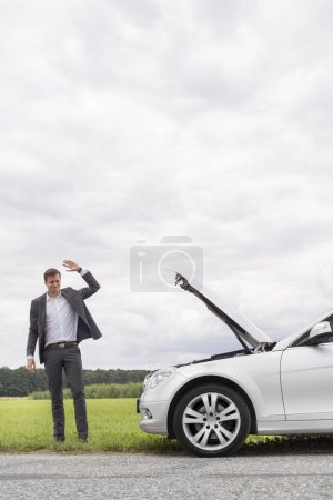 Photo for Young businessman waving for help by broken down car in countryside - Royalty Free Image