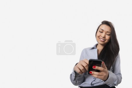 Photo for Happy businesswoman text messaging through smart phone against gray background - Royalty Free Image