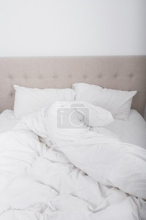 crumpled bed sheet and blanket on bed