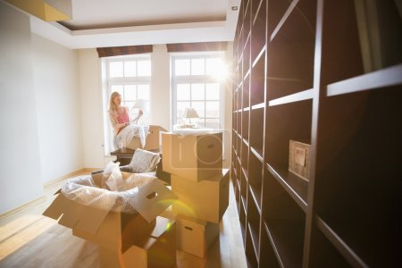 Photo for Woman unpacking lamp from moving box at new house - Royalty Free Image