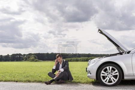 Photo for Unhappy young businessman using cell phone by broken down car in countryside - Royalty Free Image