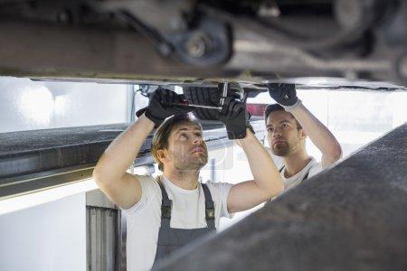 Maintenance engineers repairing car