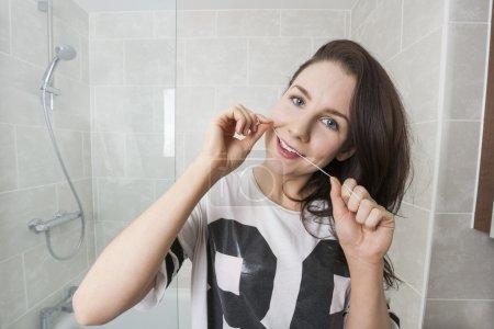 Photo pour Jeune femme soie dentaire dans la salle de bain - image libre de droit