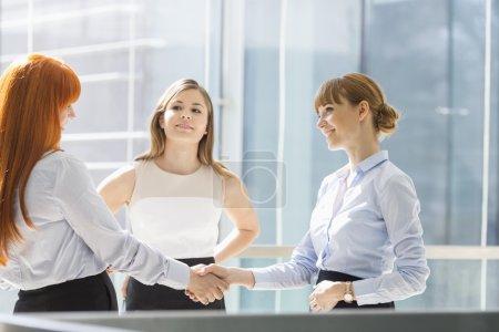 Foto de Mujeres de negocios estrechando las manos en la oficina - Imagen libre de derechos