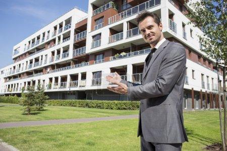 Photo pour Agent immobilier souriant présentant immeuble de bureaux - image libre de droit