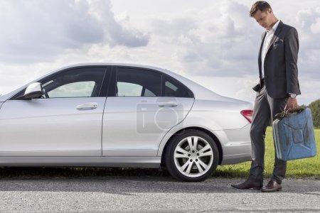 Photo pour Pleine longueur de triste jeune homme d'affaires transportant de l'essence peut en voiture en panne à la campagne - image libre de droit