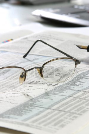 Glasses and pen  on a newspapper