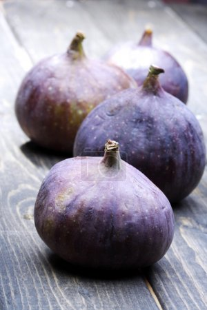 fresh purple figs on wooden table