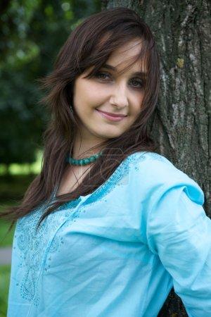 Photo pour Portrait de jeune femme debout par arbre et souriant - image libre de droit