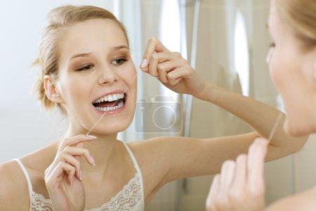 Photo pour Une jeune femme passe la soie dentaire - image libre de droit