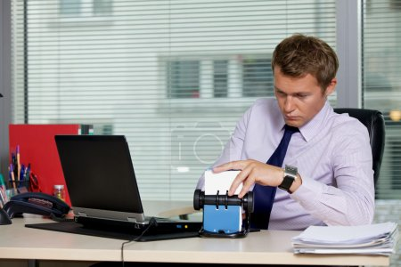 Photo for Businessman searching for card  in office - Royalty Free Image