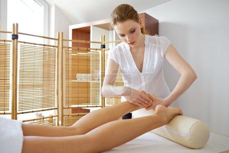 Photo pour Massage des pieds récepteur de jeune femme de masseuse - image libre de droit