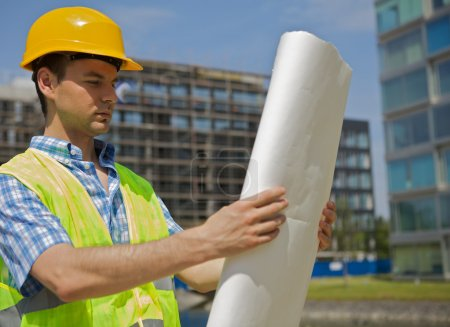 Photo for Engineer looking at blueprint on construction site - Royalty Free Image