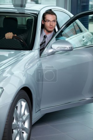Car salesperson getting in car