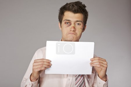 Photo for Young beaten up businessman holding  bad sales results document in hands - Royalty Free Image